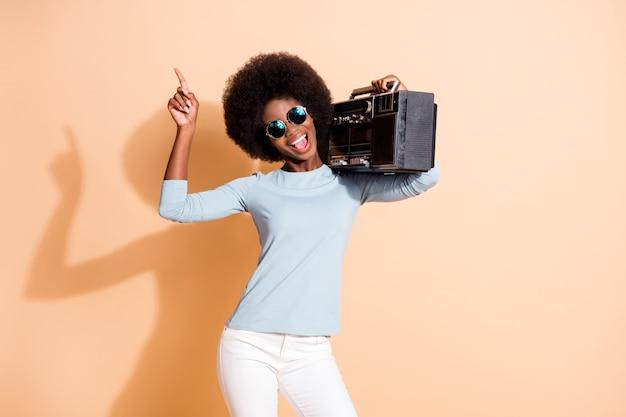 Portrait photo d'une femme brune à la peau blanche tenant une boombox près de l'oreille pointant un doigt vers le haut isolé sur fond de couleur beige pastel