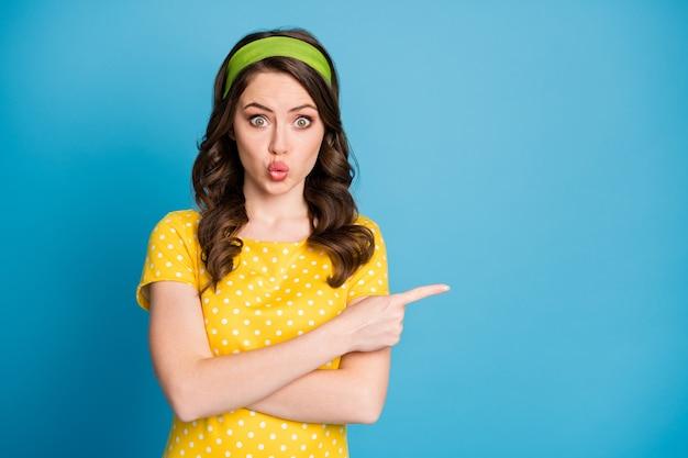 Portrait photo d'une femme choquée avec des lèvres charnues pointant le doigt sur un espace vide isolé sur fond de couleur bleu clair pastel
