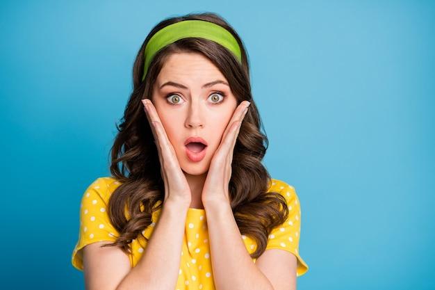 Portrait photo d'une femme choquée touchant le visage avec deux mains isolées sur fond bleu clair pastel