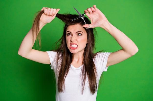 Portrait photo d'une femme en colère coupant les cheveux avec des ciseaux isolés sur fond de couleur vert vif