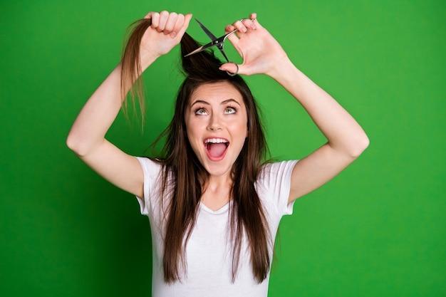 Portrait photo d'une femme excitée avec la bouche ouverte coupant les cheveux isolés sur fond de couleur vert vif