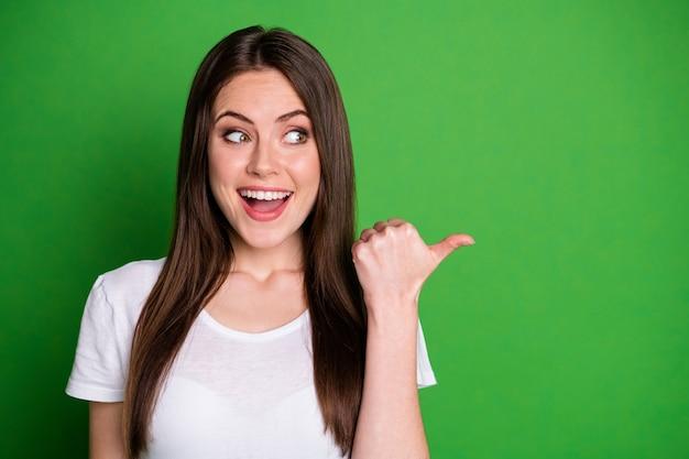 Portrait photo d'une femme excitée pointant le pouce vers le côté isolé sur fond de couleur vert vif
