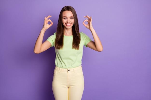 Portrait photo de femme montrant deux signes ok isolés sur fond violet vif