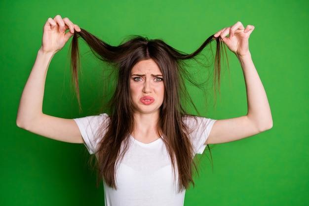 Portrait photo d'une femme offensée porter un t-shirt blanc tenant les cheveux les bras secs pointes isolées fond de couleur verte