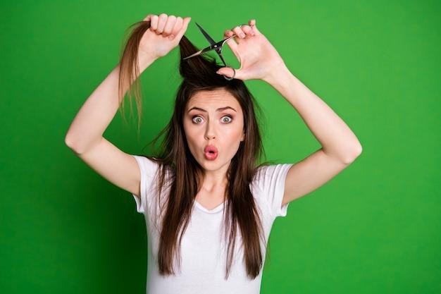 Portrait photo d'une femme surprise prête à couper ses propres cheveux isolé sur fond de couleur vert vif