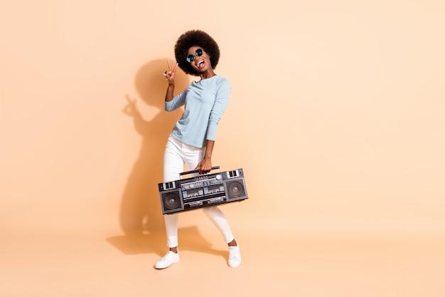 Portrait photo d'une fille afro-américaine brune montrant un signe v portant des lunettes de soleil tenue décontractée tenant une boîte à boom isolée sur fond de couleur beige pastel