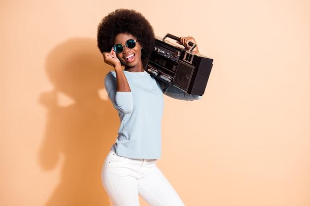 Portrait photo d'une fille afro-américaine tenant des lunettes boombox isolées sur fond de couleur beige pastel