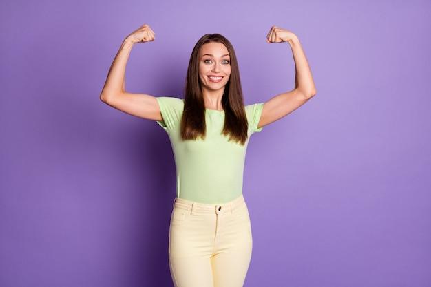 Portrait photo d'une fille forte montrant des biceps isolés sur fond violet vif