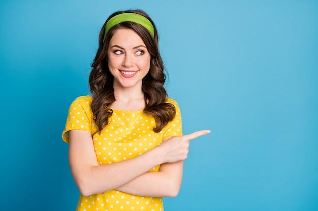 Portrait photo d'une fille heureuse pointant le doigt sur un espace vide isolé sur fond de couleur bleu clair pastel