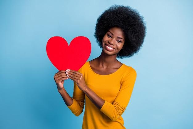 Portrait photo d'une fille à la peau noire souriante et souriante montrant le symbole du papier rouge du coeur de la saint-valentin isolé sur fond de couleur bleu vif