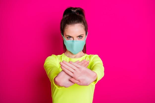 Portrait photo d'une fille portant un masque facial protecteur gardant les mains devant montrant l'arrêt isolé sur fond de couleur fuchsia vibrant