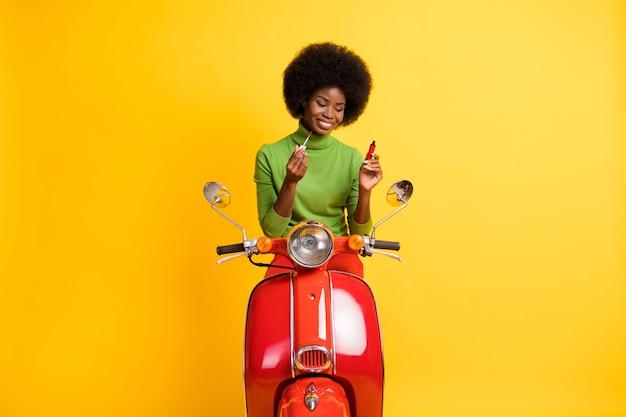 Portrait photo de jeune femme afro-américaine brune cavalier de scooter appliquant un brillant à lèvres rouge isolé sur fond de couleur jaune vif