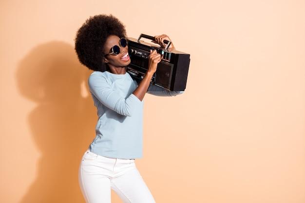 Portrait photo de jeune femme afro-américaine régulant le volume sur boombox isolé sur fond de couleur beige pastel