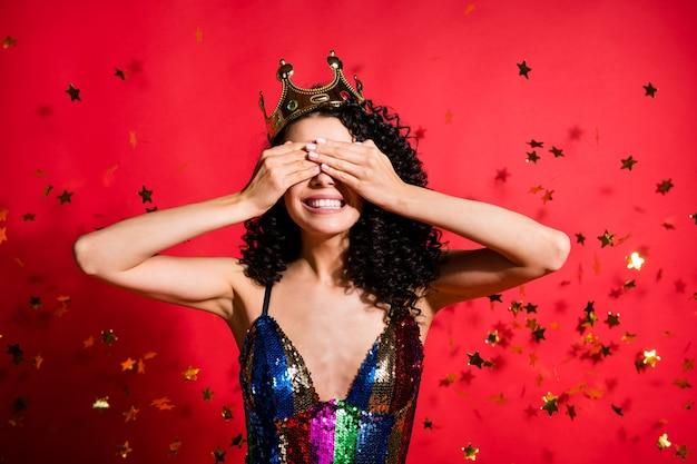 Portrait photo de jeune femme en robe pailletée glamour et couronne couvrant les yeux isolés sur fond de couleur rouge vif