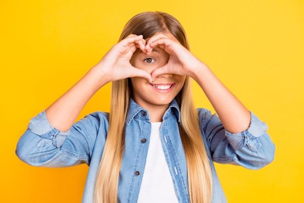 Portrait photo d'une jolie écolière montrant le coeur avec ses mains à la recherche de jeter portant une chemise en jean souriante isolée sur fond de couleur jaune vif