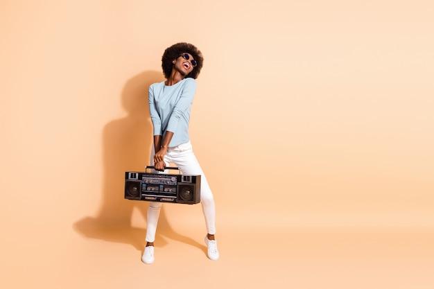 Portrait photo d'une jolie fille afro-américaine tenant un boom-box à deux mains en riant isolé sur fond de couleur beige pastel
