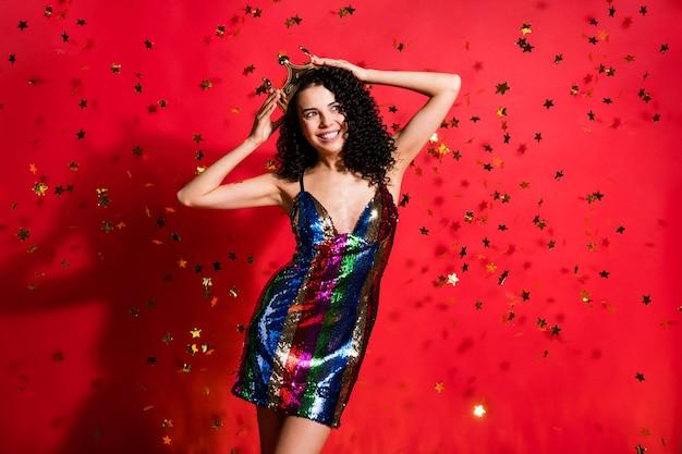 Portrait photo de luxe belle fille posant tenant la couronne avec deux mains isolées sur fond de couleur rouge vif