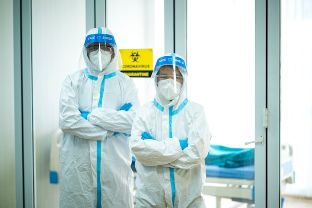 Portrait photo d'un médecin asiatique portant un costume en ppe et un masque facial à l'hôpital. virus corona, covid-19, épidémie de virus, masque médical, hôpital, quarantaine ou concept d'épidémie de virus