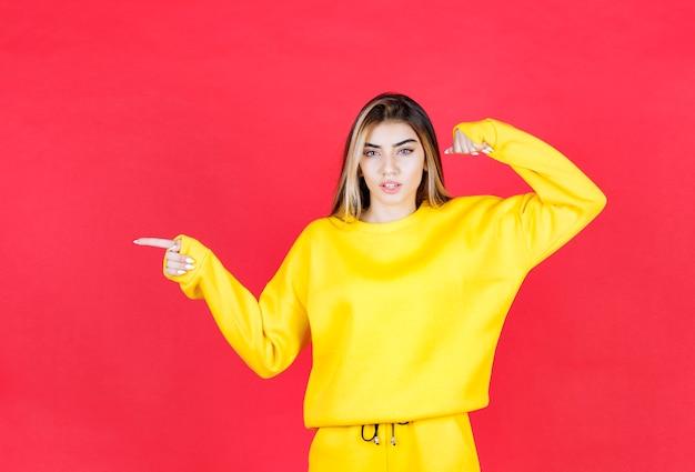 Portrait photo d'un modèle de belle fille debout et pointant de côté