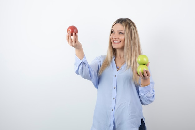 Portrait photo d'un modèle de femme assez attrayante debout et tenant des pommes fraîches.
