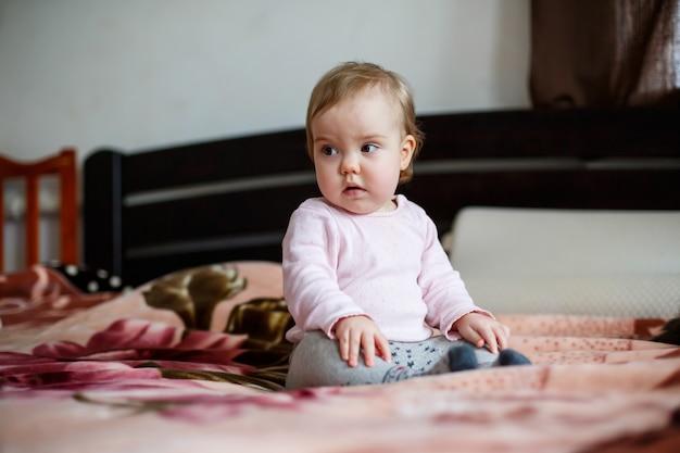 Portrait photo d'une petite fille aux joues roses, elle rampe sur le lit. enfant assis à la maison