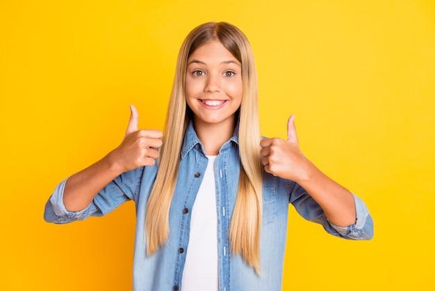 Portrait photo d'une préadolescente blonde heureuse et satisfaite montrant le pouce vers le haut sur les deux mains souriant portant une chemise en jean isolée sur fond de couleur jaune vif