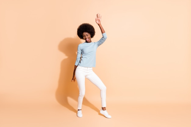 Portrait photo vue complète du corps d'une femme afro-américaine dansant isolée sur fond de couleur beige pastel