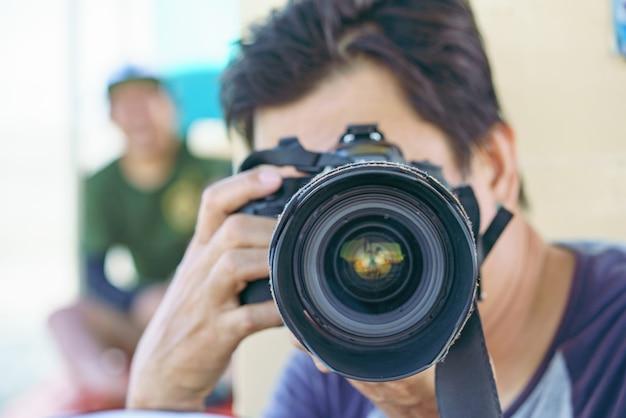 Portrait d'une photographe couvrant son visage avec l'appareil photo