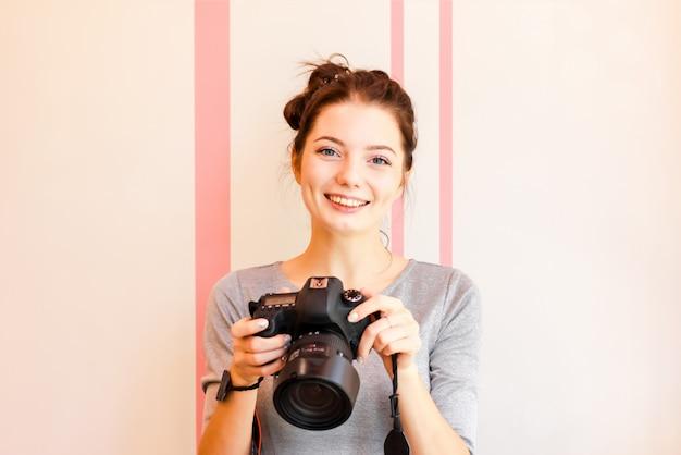 Portrait de photographe fille souriant et tenant son appareil photo