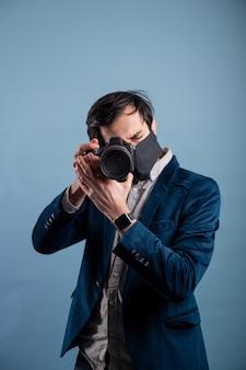 Portrait de photographe positif, homme avec masque médical tenant un appareil photo reflex numérique professionnel.