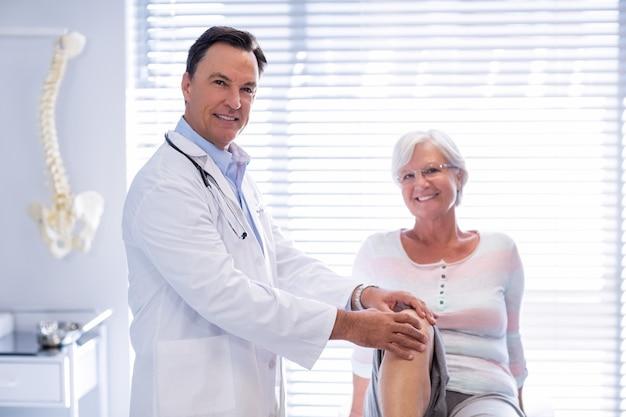 Portrait, physiothérapeute, donner, genou, thérapie, personne agee, femme