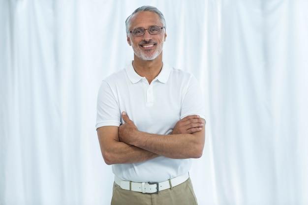 Portrait, de, physiothérapeute, sourire, et, debout, à, bras croisés, chez soi