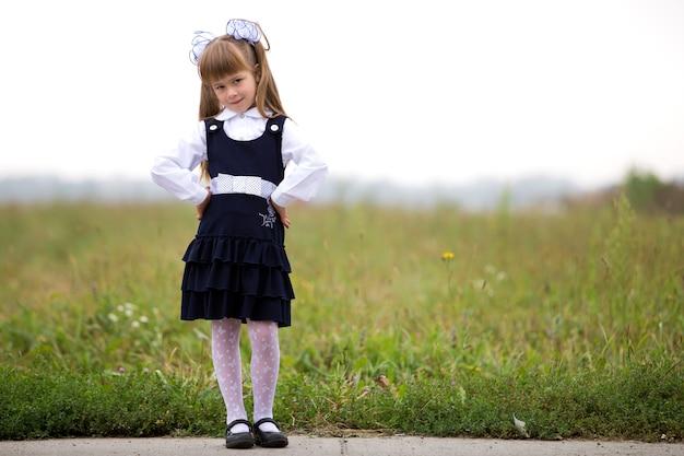 Portrait en pied de l'adorable fille de la première niveleuse sérieuse et adorable en uniforme scolaire.