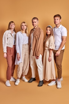 Portrait en pied d'amis étudiants calmes en vêtements à la mode posant ensemble