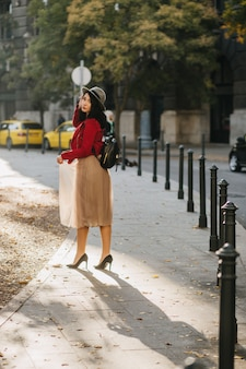 Portrait en pied de l'arrière d'une femme brune enthousiaste au chapeau élégant portant des chaussures à talons hauts noirs