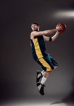 Portrait en pied d'un basketteur avec ballon