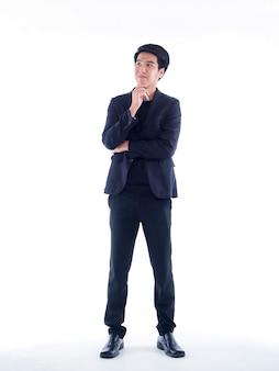Portrait en pied de beau jeune homme posant sur un mur blanc
