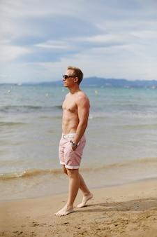 Portrait en pied d'un beau jeune homme en short de plage marchant sur la plage. mode de voyage. mode de vie sportif