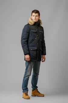 Portrait en pied de bel homme en manteau chaud qui pose en studio