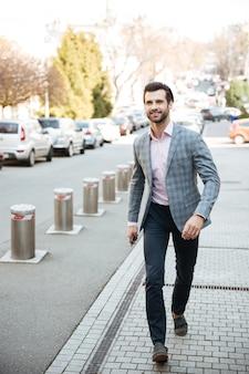 Portrait en pied d'un bel homme souriant en veste