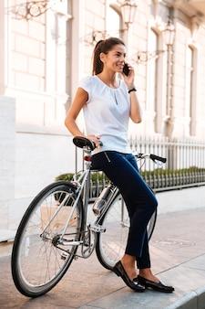 Portrait en pied d'une belle femme souriante parlant au téléphone s'appuyant sur un vélo dans la rue