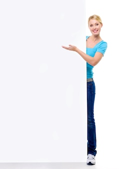 Portrait en pied d'une belle fille blonde pointe sur le panneau d'affichage