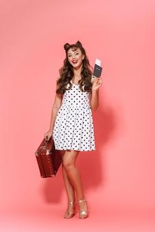 Portrait en pied d'une belle jeune fille pin-up portant une robe debout isolé, montrant un passeport avec billet d'avion, transportant une valise
