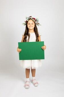 Portrait en pied d'une charmante fille d'âge préscolaire en couronne de noël et robe de fête blanche tenant...