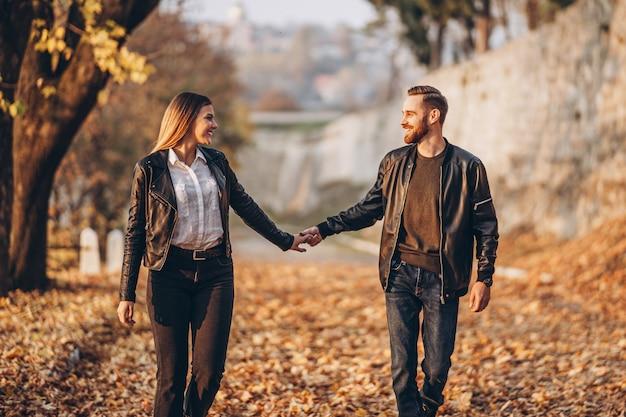 Portrait en pied d'un couple d'amoureux heureux marchant en plein air dans le parc en automne.