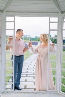Portrait en pied d'un couple élégant et mature, debout à l'extérieur d'un belvédère en bois blanc, se regardant et tenant de la lavande en fleurs dans les mains