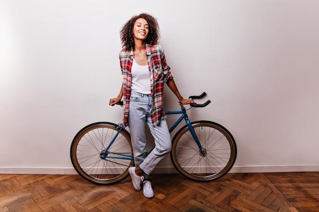 Portrait en pied d'une cycliste féminine attrayante. photo de studio d'une fille africaine intéressée en jeans debout sur blanc avec vélo.