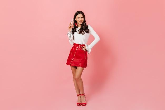 Portrait en pied de dame bouclée en jupe rouge et chaussures à talons hauts avec verre de champagne sur fond rose.
