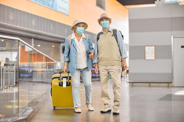 Portrait en pied d'une dame avec une valise et son époux regardant au loin