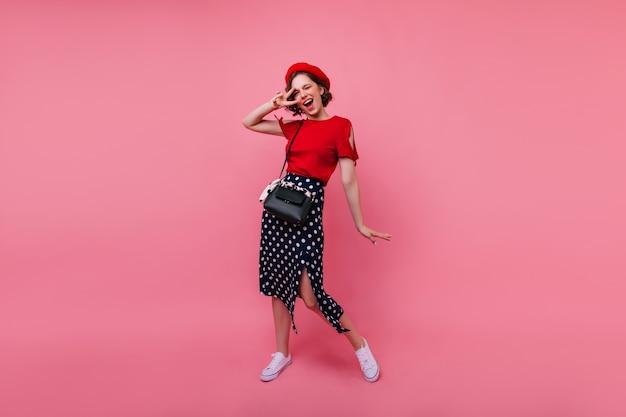 Portrait en pied du charmant modèle féminin en jupe vintage. joyeuse fille brune en béret exprimant des émotions positives.